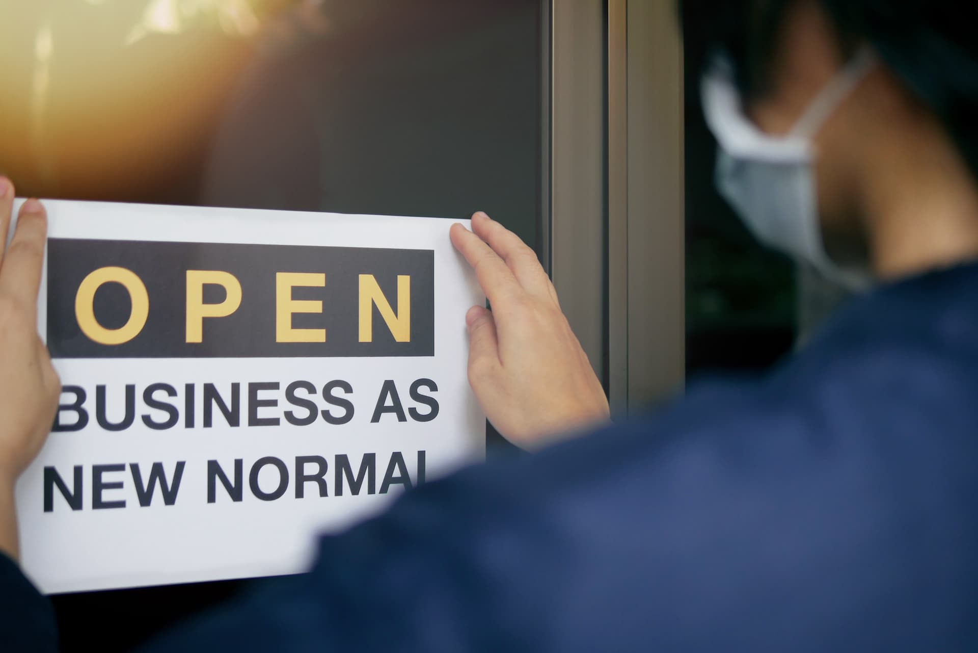 Man putting a poster on his shop door saying open business as new normal.